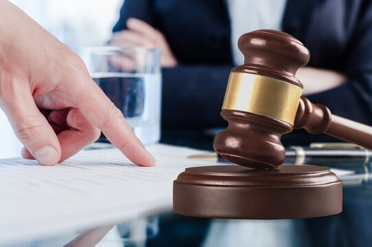 Male hand pointing a place to sign a paper and wooden gavel