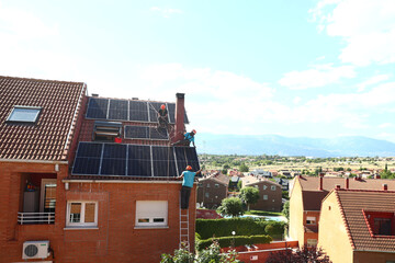 Kauahou, Navarro and Pascual, workers of the installation company Alromar, set up solar panels on the roof of a home in Colmenar Viejo
