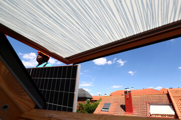 Kauahou, a worker of the installation company Alromar, stands as he sets up solar panels on the roof of a home in Colmenar Viejo