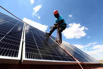 Kauahou, a worker of the installation company Alromar, sets up solar panels on the roof of a home in Colmenar Viejo
