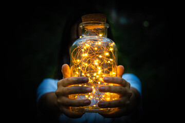 Fotomurales - Midsection Of Teenage Girl Holding Jar With Illuminated Lights