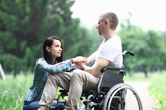 Disabled male veteran is sitting in wheelchair woman is sitting nearby. Difficulties in relationship between man and woman concept