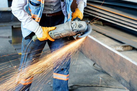 The metal worker is grinding to a steel material with a hand grinding machine in the steel factory.