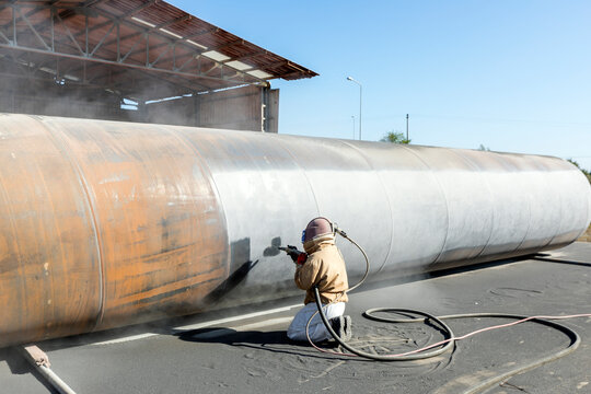 View of the manuel sandblasting to the large pipe. Abrasive blasting more commonly known as sandblasting is the operation of forcibly propelling a stream of abrasive material against a surface.
