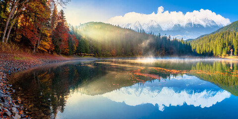 synevyr lake at foggy sunrise. misty composite landscape in mountains with snow capped tops. forest reflecting in the water. morning in fall season. trees in colorful foliage