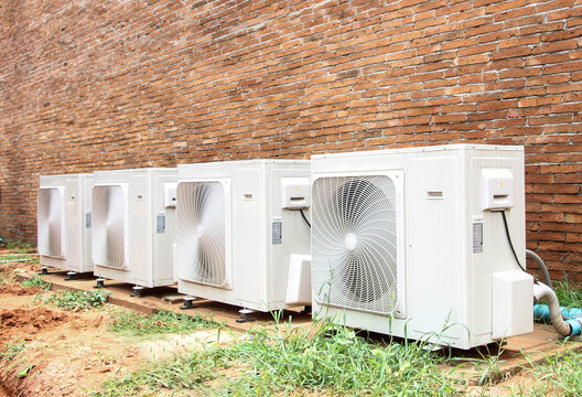 Air conditioning compressor on brick wall.