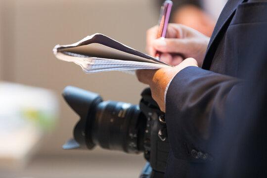 Journalist mit Kamera und Notizblock auf einem Pressetermin