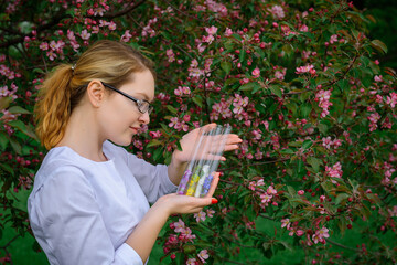 Female scientist in glasses and white coat with test tubes in her hands studies the properties of plants in botanical garden. Creating floral scents, natural cosmetics, herbal medicine, perfumes. Wall mural