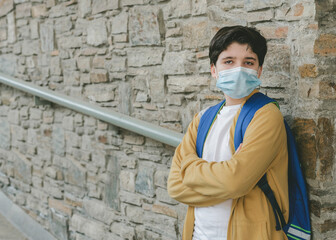 kid with medical mask and backpack waiting at the school door