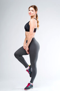 Young happy fitness girl with sporty body drink water at studio on a white background. Beautiful fit Girl. Fitness model in gray sportswear. Healthy lifestyle.