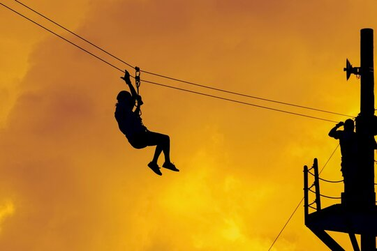 Low Angle View Of Silhouette Woman Ziplining Against Sky During Sunset