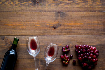 Red wine with grape - in glasses and bottle - on wooden desk top view copy space