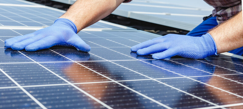 Male worker hands in glows on solar panel, technician installing solar panels on roof. Alternative energy sun energy power, ecological concept. Long web banner