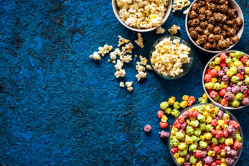 Colorful popcorn in paper box on blue background top view space for text