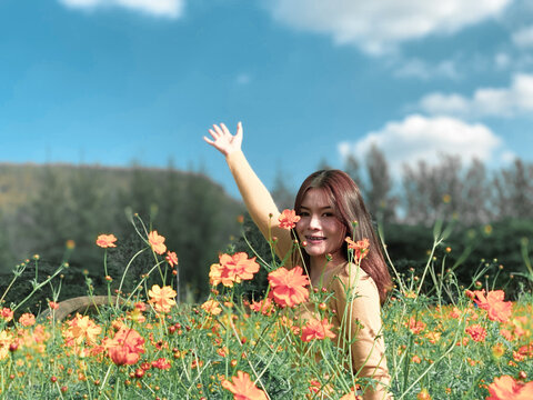 Portrait Of Happy Woman Standing Amidst Flowering Plant