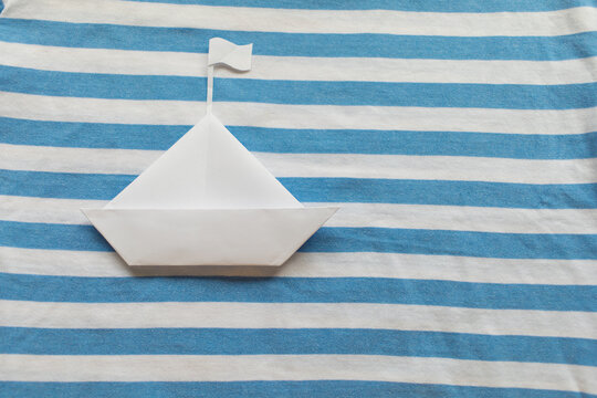 White paper ship on blue and white background with copy space