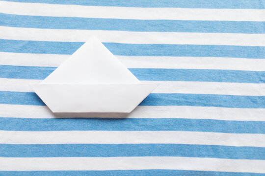 White paper ship on blue and white background. Copy space