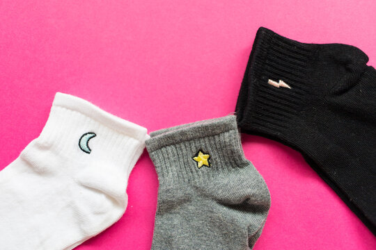 Three pair of socks in different colors on pink background. Copy space