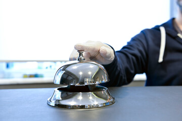 Male hand in protective gloves ringing hotel bell with copy space for your text