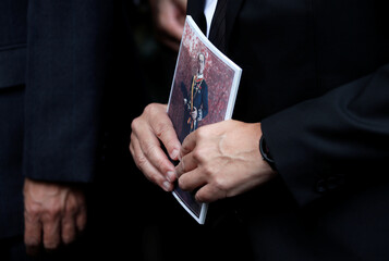 A guest holds a book with an image of Macau gambling tycoon Stanley Ho, after attending his funeral reception, in Hong Kong