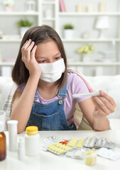 Portrait of little girl wearing facial mask with thermometer
