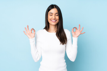 Obraz Young caucasian woman isolated on blue background in zen pose - fototapety do salonu