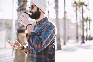 Trendy hipster guy drinking tasty coffee to go while walking down the street in sunny evening holding smartphone in hands. Caucasian male strolling outdoors with take away beverage enjoying weekend