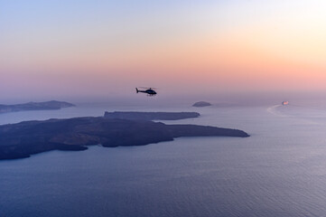 Foto auf Acrylglas Santorini Helicopter Flying Over Sea Against Sky During Sunset In Santorini.