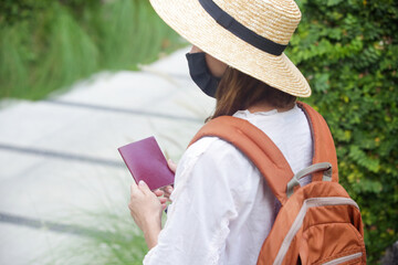Tourist woman wearing protective face mask. Woman wearing straw hat, medical mask and backpack on her summer vacation. Tourism during coronavirus outbreak.