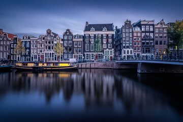 Fotomurales - Buildings By River In City Against Sky At Dusk