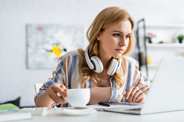 Selective focus of pretty adult freelancer holding cup and working with laptop
