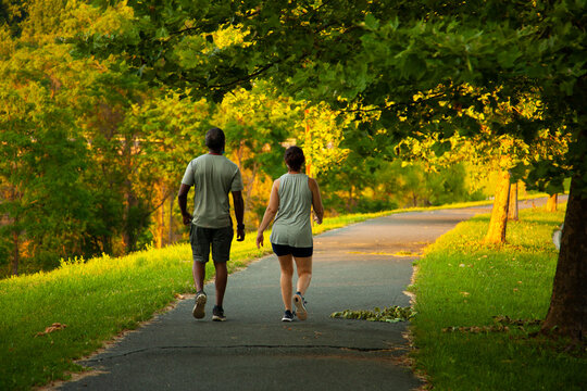 Image of an African American man and a caucasian woman walking on a hiking trail outdoors. The couple wears marching vests, shirts, shorts and sneakers. They wear face masks for COVID 19 pandemics