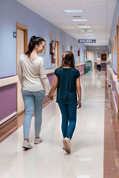 Mother and her daughter walking calmly across hospital hallway