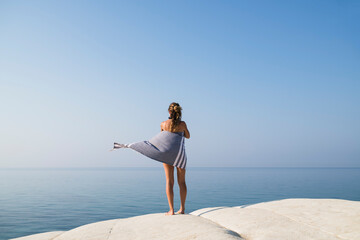 Young blonde woman relaxing on a white rock against deep blue se