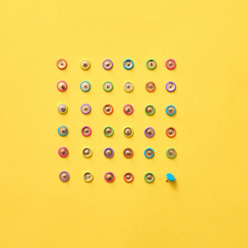 Top view of colored office stationery pins.