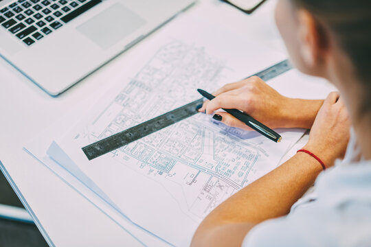 Back view of professional female engineer sitting at desktop with architectural blueprint using ruler and pen for productive work.Cropped view of young woman working at paper sketch