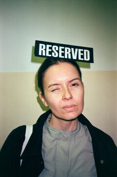 Portrait of a young woman holding a Reserved sign on her head