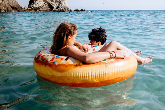 Friends enjoying in the sea in donut float
