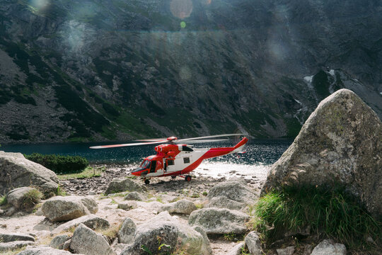 Red ambulance helicopter among mountain.