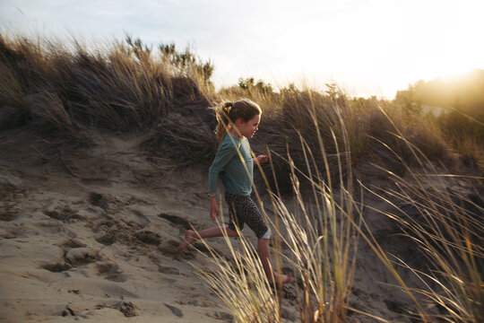 Adventurous kids exploring sand dunes in Florence Oregon at sunset