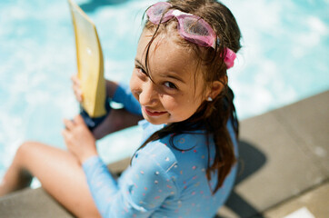 Cute young girl sitting by the side of a pool wearing swim goggles