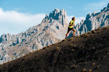 Trail runner running uphill in Collado Jermoso, Leon, Spain