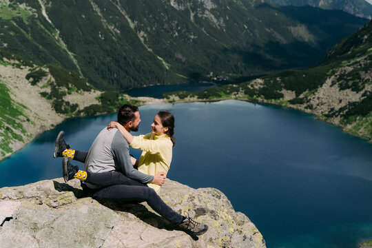 Lovely couple hugging each other on peak of mountain.