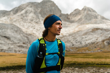 Trail runner resting in the meadows close to white limestone peaks in Picos de Europa National Park
