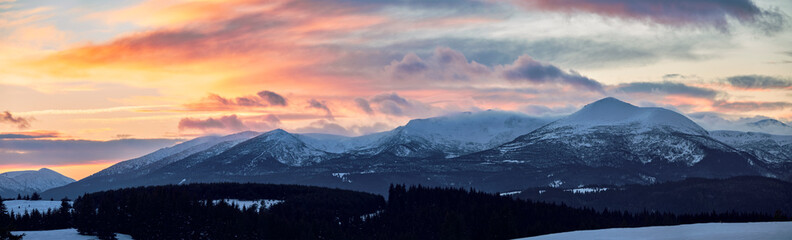 Sunset clouds over snowy mountains
