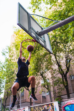 Sporty woman hanging from basketball basket
