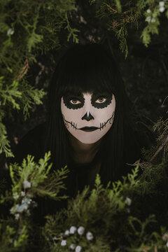 Elegant woman in Halloween black dress with sugar skull makeup
