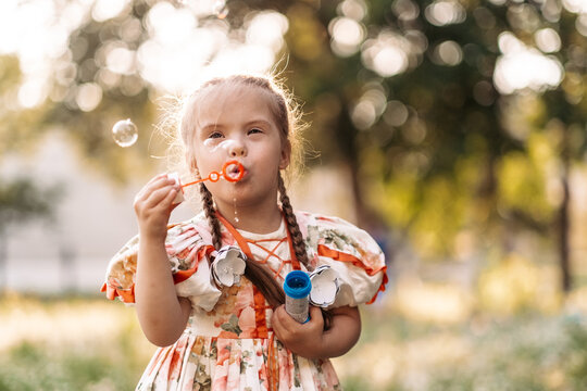 A girl with Down syndrome blows bubbles. The daily life of a child with disabilities. Chromosomal genetic disorder in a child.