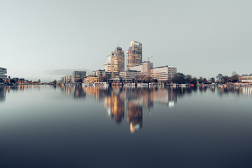 Obraz Reflection Of Buildings In River Against Clear Sky - fototapety do salonu