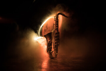 Photo sur Aluminium Musique Alto gold sax miniature with colorful toned light on foggy background. Saxophone music instrument in lowlight. Selective focus